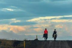 Dois povos que montam dois cavalos na estrada em Islândia fotos de stock royalty free