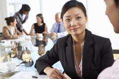 Dois povos que têm a reunião em torno da tabela de vidro na sala de reuniões com os colegas no fundo Imagens de Stock Royalty Free