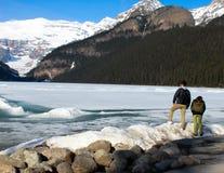 Dois povos que veem Lake Louise e montanhas Fotografia de Stock Royalty Free