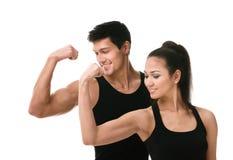 Dois povos sportive no preto que mostra o bíceps fotos de stock