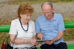 Dois povos superiores que sentam-se com um PC da tabuleta Fotografia de Stock