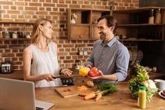 Dois povos vívidos que têm o divertimento na cozinha foto de stock