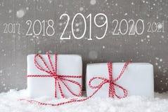 Dois presentes com flocos de neve, texto 2019, fundo nevado do cimento fotos de stock