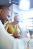 Dois proprietários empresariais pequenos millenial criativos que trabalham na estratégia social dos meios usando uma tabuleta dig Foto de Stock Royalty Free