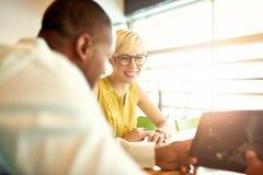 Dois proprietários empresariais pequenos millenial criativos que trabalham na estratégia social dos meios usando uma tabuleta dig Imagem de Stock