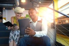 Dois proprietários empresariais pequenos millenial criativos que trabalham na estratégia social dos meios usando uma tabuleta dig Fotos de Stock Royalty Free