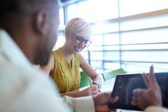 Dois proprietários empresariais pequenos millenial criativos que trabalham na estratégia social dos meios usando uma tabuleta dig Imagens de Stock
