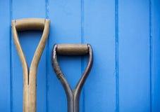 Dois punhos da ferramenta de jardim sustentados acima contra uma porta azul pintada foto de stock
