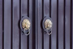 Dois puxadores da porta de bronze marrons com uma cabeça do leão em uma porta do metal imagem de stock