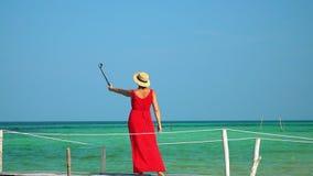 Dois quadros no vídeo Mulher bonita que anda abaixo do cais no vestido vermelho longo Ilha de Phu Quoc A mulher aprecia vistas do video estoque