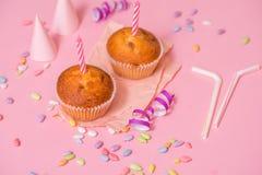 dois queques do chocolate, uma vela do aniversário Partido para meninas Tampões e ouropel e doces multi-coloridos em um fundo cor Foto de Stock Royalty Free