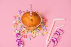 dois queques do chocolate, uma vela do aniversário Partido para meninas Tampões e ouropel e doces multi-coloridos em um fundo cor Imagens de Stock Royalty Free