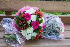 Dois ramalhetes das rosas em um banco Foto de Stock Royalty Free