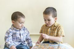 Dois rapazes pequenos bonitos estão estudando um livro Dois rapazes pequenos nas camisas com um livro Conceito da instrução Imagens de Stock Royalty Free