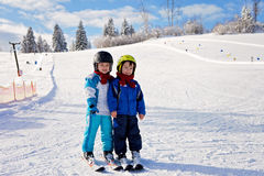 Dois rapazes pequenos bonitos, irmãos, esquiando em um dia ensolarado Fotografia de Stock