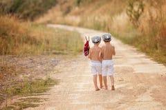 Dois rapazes pequenos bonitos, irmãos, guardando um pacote, comendo o pão Imagem de Stock