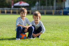 Dois rapazes pequenos bonitos, jogando o futebol Foto de Stock