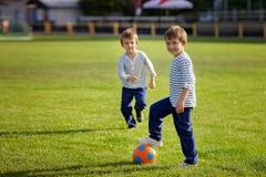 Dois rapazes pequenos bonitos, jogando o futebol Imagem de Stock