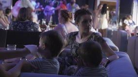 Dois rapazes pequenos com a mãe no restaurante Evento das crianças celebration Povos vídeos de arquivo