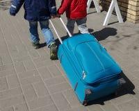 Dois rapazes pequenos com a mala de viagem grande que vai à viagem Fotografia de Stock