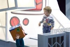 Dois rapazes pequenos comunicam-se em uma exposição dos robôs foto de stock