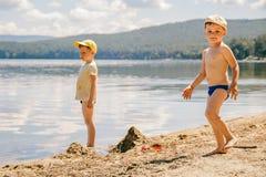 Dois rapazes pequenos nos tampões estão na costa arenosa do lago imagens de stock