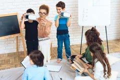 Dois rapazes pequenos obtêm familiares com a tecnologia da realidade virtual na sala de aula fotografia de stock