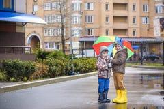 Dois rapazes pequenos, ocupa em uma poça, com guarda-chuvas pequenos Foto de Stock Royalty Free