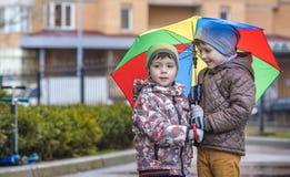 Dois rapazes pequenos, ocupa em uma poça, com guarda-chuvas pequenos Imagem de Stock