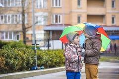 Dois rapazes pequenos, ocupa em uma poça, com guarda-chuvas pequenos Imagens de Stock Royalty Free