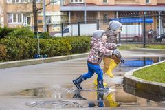 Dois rapazes pequenos, ocupa em uma poça, com guarda-chuvas pequenos Imagem de Stock Royalty Free