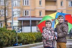 Dois rapazes pequenos, ocupa em uma poça, com guarda-chuvas pequenos Imagens de Stock