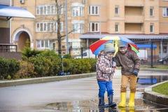 Dois rapazes pequenos, ocupa em uma poça, com guarda-chuvas pequenos Fotografia de Stock Royalty Free