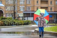 Dois rapazes pequenos, ocupa em uma poça, com guarda-chuvas pequenos Fotografia de Stock