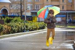 Dois rapazes pequenos, ocupa em uma poça, com guarda-chuvas pequenos Fotos de Stock Royalty Free