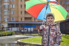 Dois rapazes pequenos, ocupa em uma poça, com guarda-chuvas pequenos Fotos de Stock