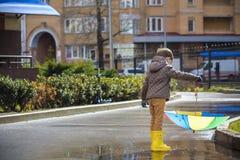 Dois rapazes pequenos, ocupa em uma poça, com guarda-chuvas pequenos Foto de Stock