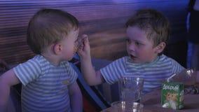 Dois rapazes pequenos que alimentam-se no restaurante Evento das crianças celebration filme