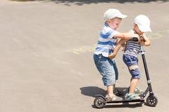 Dois rapazes pequenos que apreciam um passeio do 'trotinette' Imagens de Stock