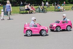 Dois rapazes pequenos que conduzem carros bondes do brinquedo em um parque imagem de stock royalty free