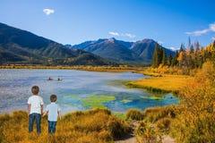 Dois rapazes pequenos que guardam as mãos no lago Imagens de Stock Royalty Free