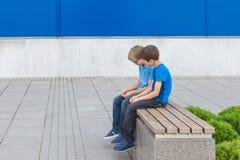 Dois rapazes pequenos que jogam com o telefone celular que senta-se no banco fora Foto de Stock