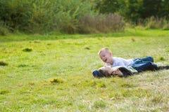 Dois rapazes pequenos que jogam em um campo de grama fotos de stock royalty free