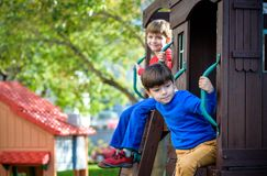 Dois rapazes pequenos que jogam junto e que têm o divertimento Momento da família do estilo de vida dos irmãos no campo de jogos  imagem de stock royalty free