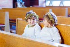 Dois rapazes pequenos que jogam um anjo da história do Natal na igreja Fotografia de Stock Royalty Free