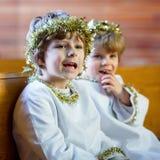 Dois rapazes pequenos que jogam um anjo da história do Natal na igreja Fotos de Stock