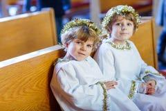 Dois rapazes pequenos que jogam um anjo da história do Natal na igreja Imagens de Stock