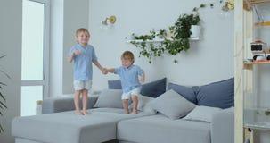 Dois rapazes pequenos que saltam no sof? e que t?m o divertimento Alegria, riso e divertimento em casa