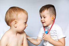 Dois rapazes pequenos que usam o estetoscópio Crianças que jogam o doutor e o paciente Verifique a pulsação do coração fotos de stock royalty free