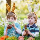 Dois rapazes pequenos que vestem as orelhas do coelhinho da Páscoa e que comem o chocolate Fotos de Stock Royalty Free